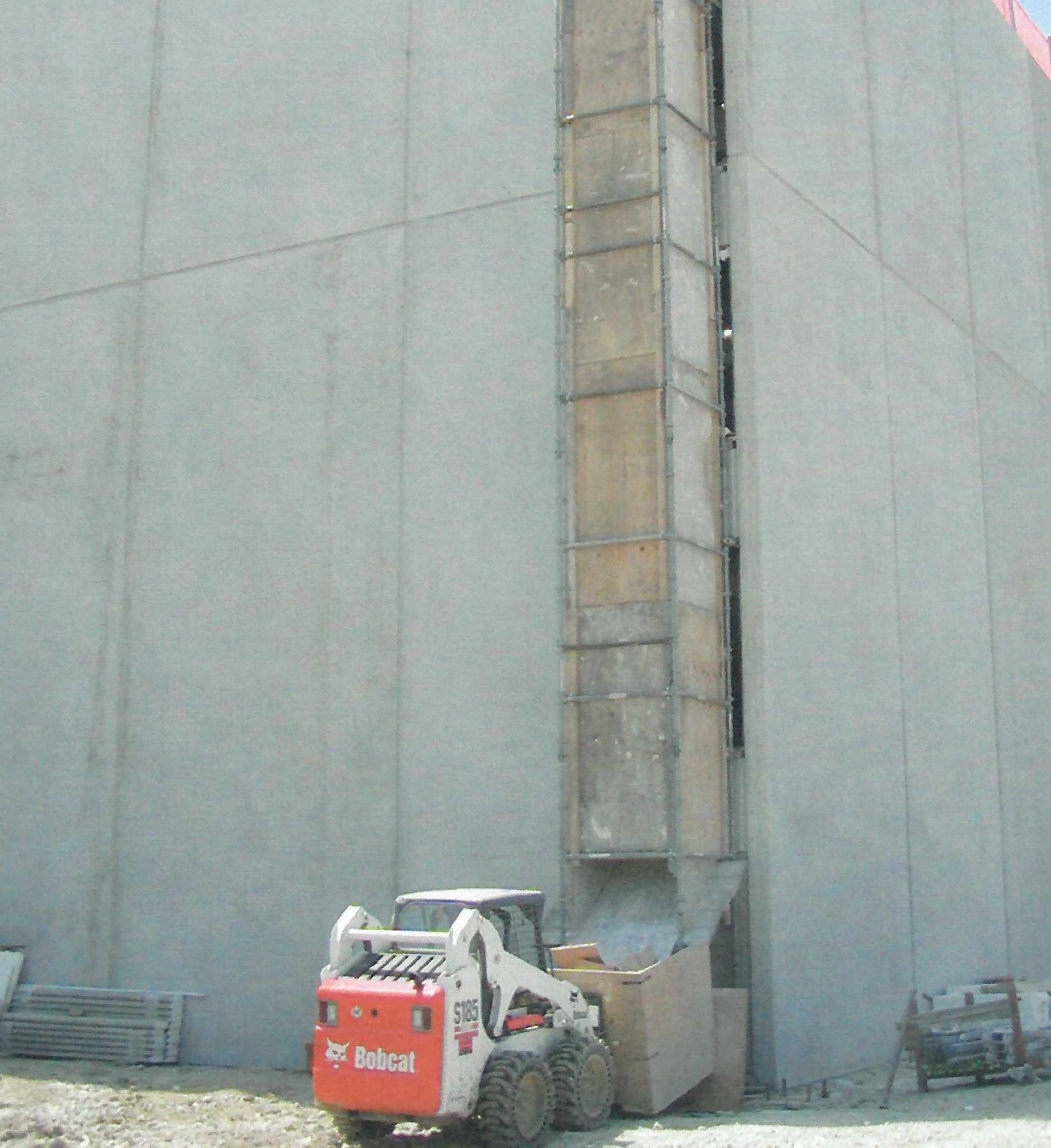 debris trash chute pictured on the exterior of a building under construction - International Equipment